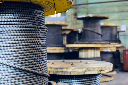 Carretes de cable grandes almacenados en las instalaciones de la fábrica. taller de producción de eslingas de cable. Foto de archivo - 67452685