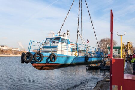 MOSCOW, RUSSIA - NOVEMBER 11, 2016: State Unitary Enterprise Mosvodostok performs recovery vessels on coastal winter parking. The ship hangs on four chain slings cargo. Editorial
