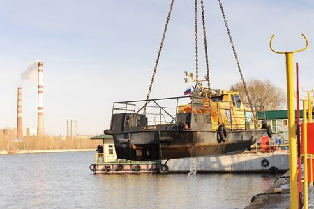MOSCOW, RUSSIA - NOVEMBER 11, 2016: State Unitary Enterprise Mosvodostok performs recovery vessels on coastal winter parking. The ship suspended from a chain slings. Editorial