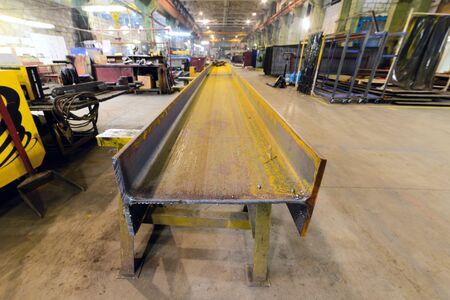 ferrous: Rusty steel I-beams. Plot welding machine factory.