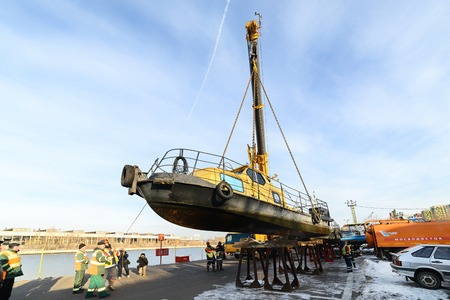 MOSCOW, RUSSIA - NOVEMBER 11, 2016: State Unitary Enterprise Mosvodostok performs recovery vessels on coastal winter parking. Truck crane lowers the vessel to metal supports Editorial