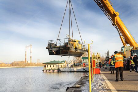 MOSCOW, RUSSIA - NOVEMBER 11, 2016: State Unitary Enterprise Mosvodostok performs recovery vessels on coastal winter parking. River vessel carries a crane. Editorial