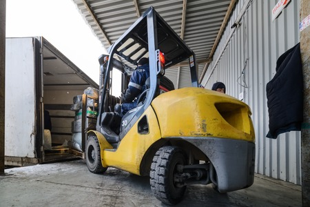 Forklift is putting cargo to truck outdoors