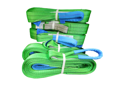 Green nylon soft lifting slings stacked in piles.