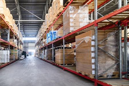 Grandes almacenes de hangares industriales y empresas de logística. Cajas y contenedores con productos colocados en estantes altos.
