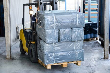 polyethylene film: Electric forklift carries boxes. Cargo packed in polyethylene film gray. Stock Photo