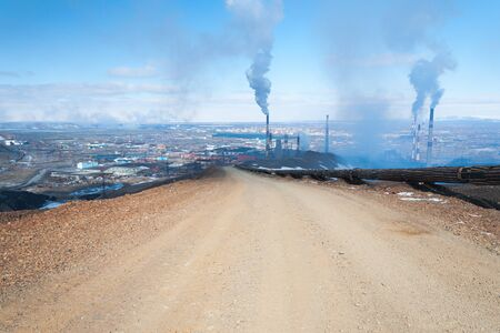 Mountain gravel road. The wide road leads to the smelter. Industrial peyzhaz.