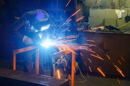 welds: Working welder welds parts factory Stock Photo