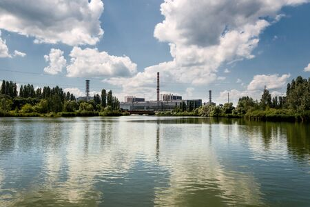 Kursk Nuclear Power Plant reflected in a calm water surface.