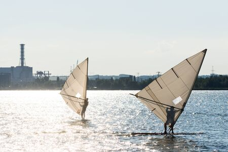 Windsurfers are trained on a large lake.