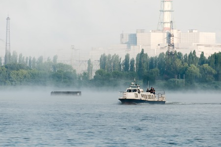 Pleasure boat floating in the reservoir power plant. Foggy morning. Editorial