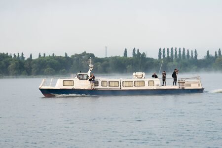 npp: Kurchatov, Russia - JUNE 23, 2016: Reporters sail on a pleasure boat on the reservoir of Kursk NPP. Foggy morning.