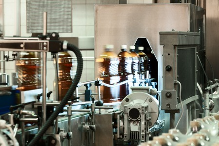 inclusions: Plastic bottles filled with beer on the conveyor of the filling machine. Stock Photo