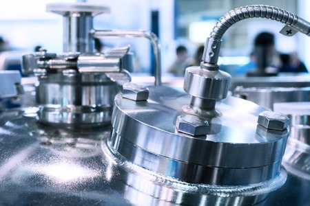 Glossy metal flanges on the body of the pharmaceutical reactor Stock Photo