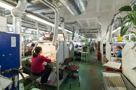 famous industries: Shoe factory. Female worker on a sewing machine. Editorial