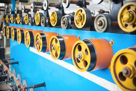 Rotating rubberized wheels of the winding machine.