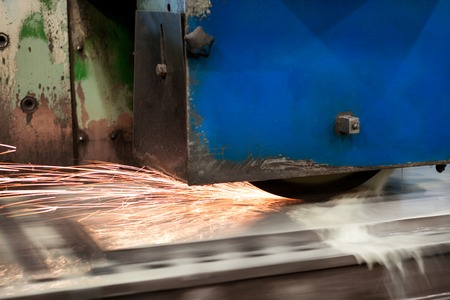 Work of an industrial surface grinding machine. Grinding of a flat metal part.