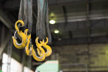 Varios ganchos amarillos de carga que cuelgan en eslingas textiles sucias y aceitado. Foto de archivo - 84573234
