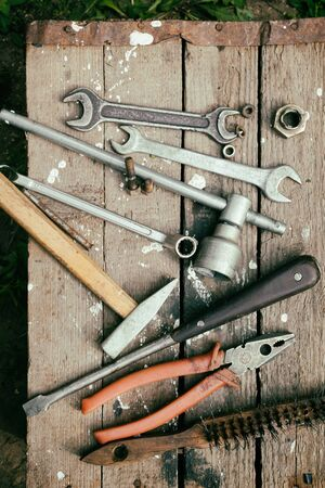 garage: On weathered old wooden surface lie the tools