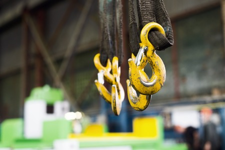 Several yellow cargo hooks hanging on dirty, oiled textile slings.