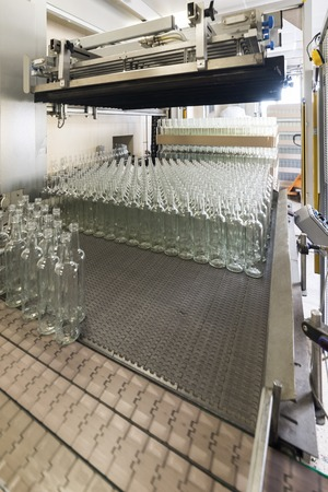 Automatic machine places empty glass bottles on a conveyor.