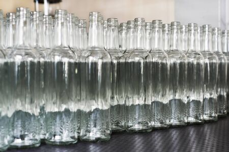 A lot of empty glass bottles on the conveyor Stock Photo