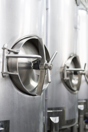 round: A lot of stainless steel tanks with large round hatches, modern beverage production.