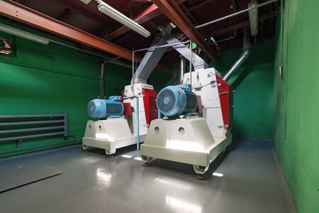 Rotary hammer mills for grinding wheat and barley grain.