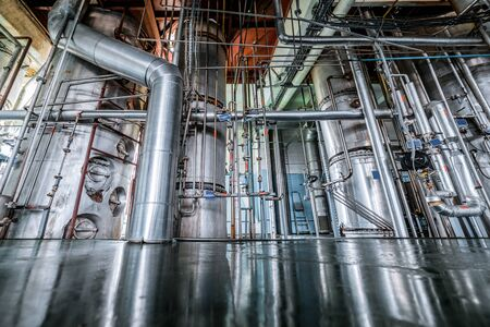 Silvery distillation columns entangled in a multitude of pipes, valves and sensors. Reklamní fotografie - 89325995