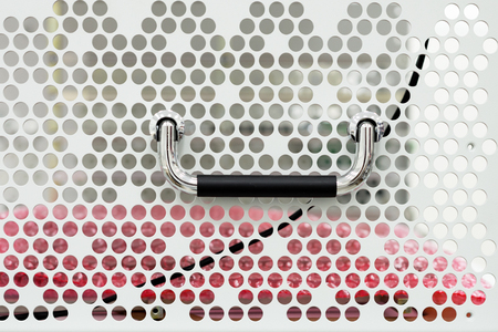 Steel perforated housing wall for electrical equipment. Archivio Fotografico