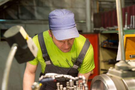 turner: LIPETSK, RUSSIA - JUNE 15, 2017: Lipetsk Machine Tool Plant, A young turner processes a metal workpiece on a mechanical lathe. Editorial