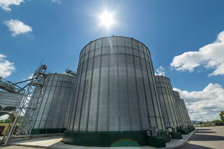 The modern granary. High metal silos for storage of wheat and barley. Sunny day, the blue sky. Stock Photo