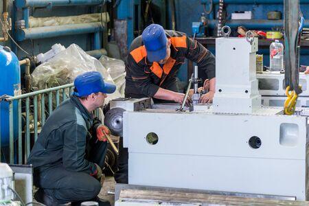 Schlosser arbeiten an der Montage einer neuen Metall-Schneidemaschine. Standard-Bild - 90561549