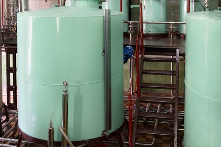Large riveted metallic cisterns of light green color. Manufacture of alcoholic beverages.