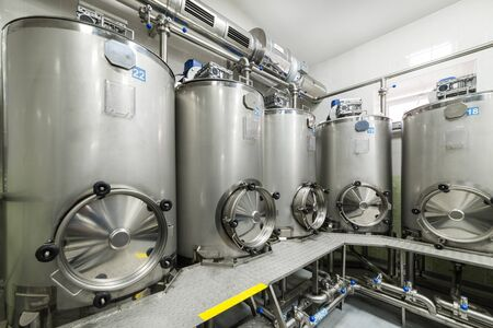 A lot of stainless steel tanks with large round hatches, modern beverage production.