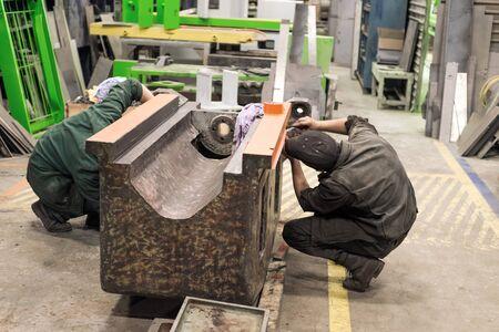 Lipetsk, Russland - 15. Juni 2017: Lipetsk-Werkzeugmaschinenfabrik. Vorbereitung des Bettes einer spanenden Maschine für die Montage. Schlosser inspizieren den Rahmen. Standard-Bild - 93499279
