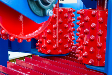Feeding mechanism sawmill. Powerful metal rollers with spikes. Woodworking equipment.