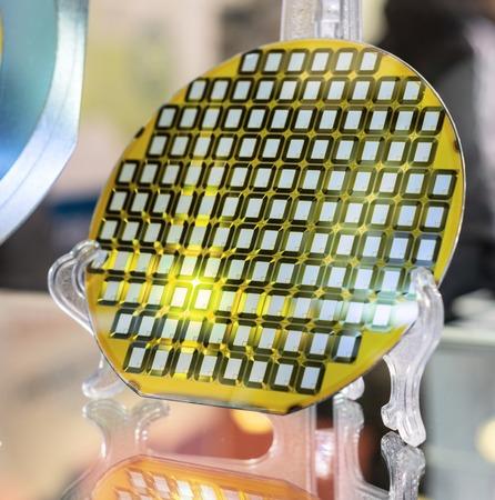 Oblea de silicio, detalle de una oblea de silicio que refleja diferentes colores