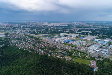 Aerial view of wheat fields, meadow, forest andindustrial warehouses in rural Russia.