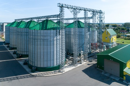 The modern granary. Metal silos with green roofs. Stock Photo