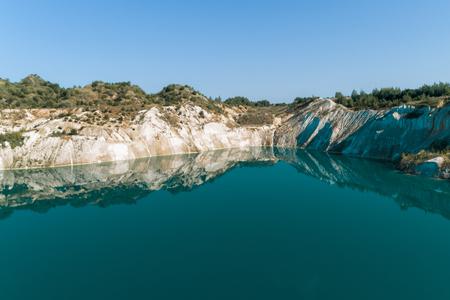 Stary kamieniołom gipsu wypełniony niebieską i czystą wodą. Widok z lotu ptaka, od góry do dołu