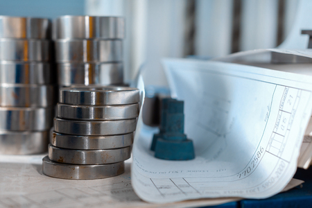 Metal rings, the production of metalworking machine. Items are stacked, next are paper drawings Фото со стока