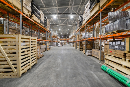 Long shelves with a variety of boxes and containers. Фото со стока