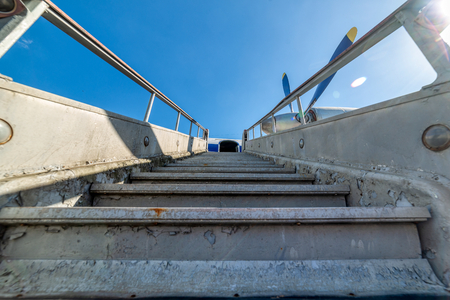 Old, worn passenger gangway. Gangway attached to the aircraft