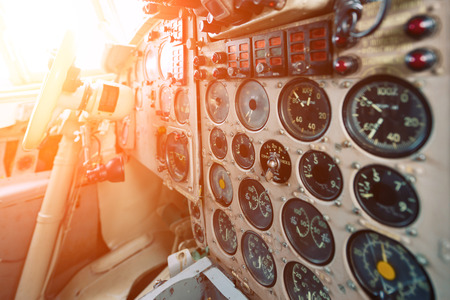 Dashboard of an old airplane. Many analog pointers, buttons and switches