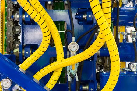 Fragmento de un potente equipo de perforación. Mangueras hidráulicas amarillas, estructura de acero, manómetro