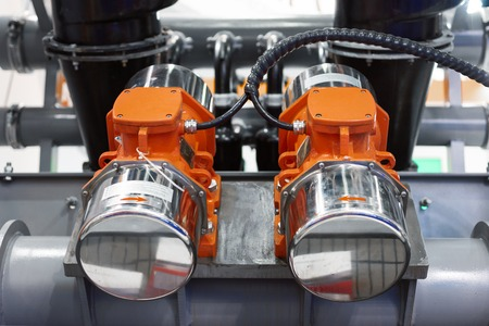 Industrial vibromotors mounted on the pipework of the system of vibrating transport