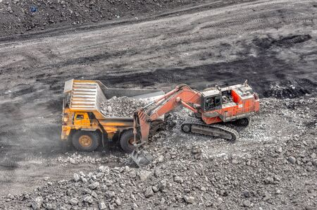 Coal mining in a quarry. A hydraulic excavator loads a dump truck. Loading of coal into the body of a truck.