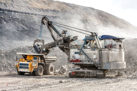 Ore loading with a powerful excavator. Loading a large mining truck.