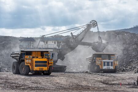Ore loading with a powerful excavator. Loading a large mining truck. Banco de Imagens